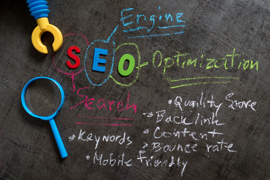 seo-search-engine-optimization-concept-as-colorful-alphabet-seo-handwriting-explanation-with-color-chalk-robot-arm-and-magnifying-glass-on-blackboard-wallpaper